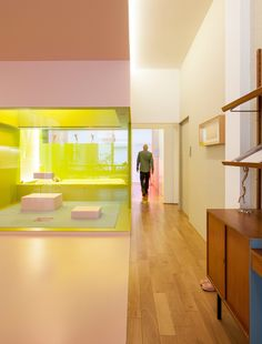 In the upstairs apartment, glass partitions keep the elongated loft open and spacious, while lighting is placed against brightly colored walls to create a cool, atmospheric glow.