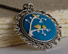 Blue polymer clay cabochon pendant with yellow birds and white branches