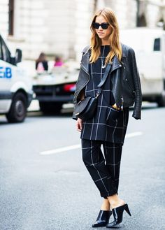A black leather jacket is paired with a navy top and bottom, a black cross-body bag, and black mules
