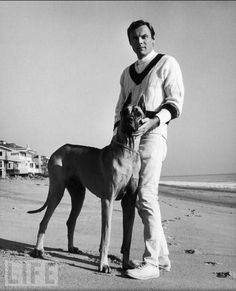 """Adam West, the actor, best known for playing Batman on TV, poses with a Great Dane he calls """"Batdog,"""" circa 1967."""