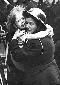 A female warden carrying a little girl after she had been rescued from a house hit by a doodlebug.