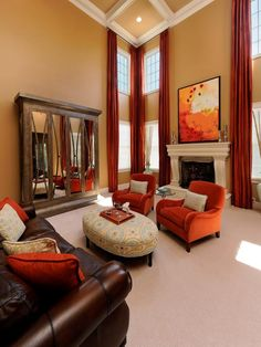 HGTV shows how high coffered ceilings open up a neutral living room with orange curtains, orange chairs, and orange artwork over a white traditional fireplace.