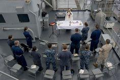 U.S. Navy Chaplain Lt. Tung Tran blesses communion during Roman Catholic Mass aboard the amphibious dock landing ship USS Rushmore. #Navy #USNavy #AmericasNavy navy.com