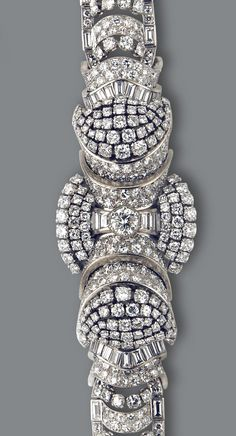 A diamond bracelet, French, circa 1950  centering a round brilliant-cut diamond within an elaborate surround of pavé-set diamond articulated panels accented by rows of round brilliant and baguette-cuts, completed by a tapered bracelet of similar design; with French assay marks; estimated total diamond weight: 25.00 carats; mounted in eighteen karat gold and platinum; length: 6 1/2in.