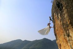 Zheng Feng, an amateur climber takes wedding pictures with his bride on a cliff in Jinhua, Zhejiang province