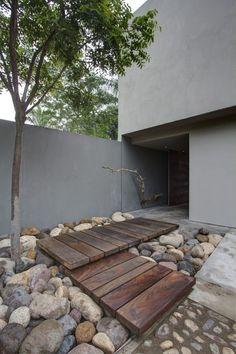 Una entrada a vivienda con estilo. Madera y piedras en armonía acompañadas por un árbol.