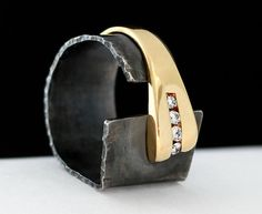 Hammered and oxidized sterling silver with 14 kt yellow gold and four brilliant cut diamonds.