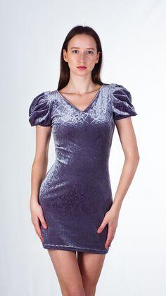 Короткое вечернее платье, облегающего кроя. Модель с глубоким V-образным вырезом. Рукав укороченный, объемный, по типу фонарика. Платье декорировано сборками-буфами на рукавах и талии изделия, образующими красивые складки.