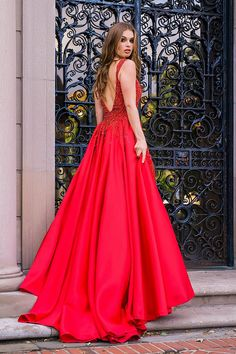 9a3600a7822 Red long fitted embellished sleeveless gown with an over skirt.