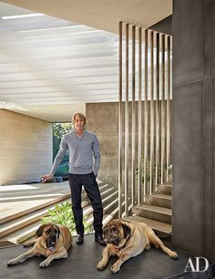 Michael Bay is flanked by his English mastiffs, Rebel (left) and Bonecrusher, in the entry of his home designed by Miami architect Chad Oppenheim of Oppenheim Architecture + Design