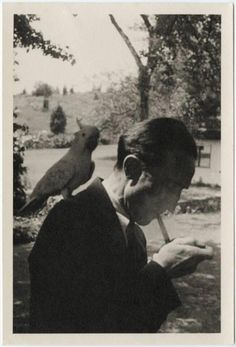 Marcel Duchamp lighting a cigarette with a bird on his shoulder