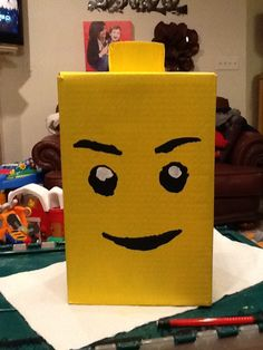 How to make a Lego Valentine box. So easy! Start with a box, tape an empty duct tape shell to the top. Put several coats of yellow acrylic over box. Print out a face and cut out to make a stencil. Let kids paint. Cut whole in side for Valentines to fit.