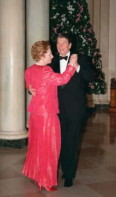 British Prime Minister Margaret Thatcher dances with US President Ronald Reagan in a bright pink gown