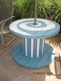 Painted an old wooden spool and, with a patio umbrella we found on clearance, made a cute outdoor table for by the pool!: