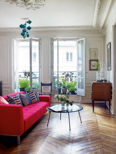 Herringbone floor with bright pink sofa.  I also love the long, vertical windows.