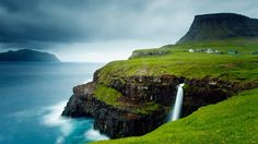 Village of Gásadalur below Heinanova mountain, with waterfall cascading over cliff into the Atlantic Ocean, Vágar, Faroe Islands