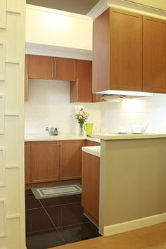 The kitchen reflects the homeowner's quiet and conservative demeanor, with wooden cabinets and a white-tiled backsplash that works to lighten the space. Overhead cupboards are a great idea to maximize space and make room for more storage in a cramped apartment.