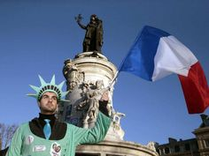 A man, dressed as the Statue of Liberty holds up the French national flag at the Place de la Republique,  on January 11, 2015 .