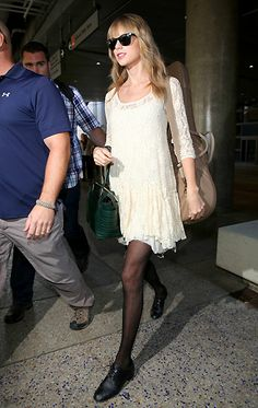 Taylor Swift was low-key arriving at LAX in shades, an off-white lace dress and tights on Oct. 22.