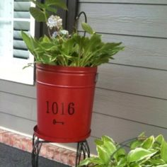 Repurposed popcorn tin. Add a coat of paint & sharpie your house number on the front. Punch several holes in bottom for drainage, use the lid underneath to catch water.