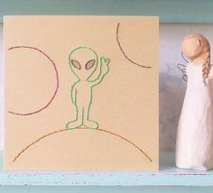 "Hand Stitched Alien. ​ The perfect card for anyone who is mad about Sci fi, this cheeky little chap is sure to make them smile. ​The design has been sewn in a whipped running stitch and back stitch throughout, directly onto a light brown card.  The card comes with an envelope to match and is left blank inside for your own message. Card measures : 6 "" by 6 "".  Free gift tag included.  ​Copyright LilianAlice Ltd. 2016."