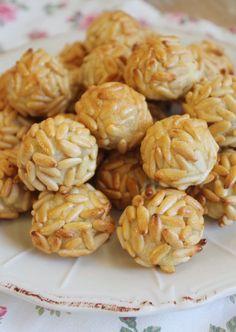 Panellets aux Amandes et Pignons  -150g de poudre d'amandes -85g de sucre -55g de blancs d'œuf -150g de pignons de pin  Mettre le sucre et la poudre d'amandes dans un récipient. Mélanger et ajouter le  blanc d'œuf. Diviser la pâte en boulettes de 12 g environ. Cuisson:  20 minutes jusqu'à ce que les pignons soient bien dorés