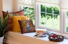 I love this little corner - a window seat with cosy cushion, books to read and a pot of sweet tea