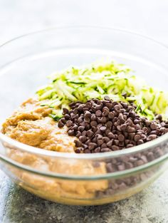 clear mixing bowl with shredded zucchini, chocolate chips, and mashed bananas