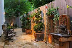 Flagstone terrace enclosed with wood privacy fence. Spance for planters and topiaries among evenly spaced landscape lights. Electrical set for fountain. Rock edge planting bed with automatic sprinkler.