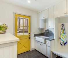 An eye-catching yellow dutch door opens to a beach style laundry room and mudroo. An eye-catching yellow dutch door opens to a beach style laundry room and mudroo. An eye-catching yellow dutch door op. Dutch Door Interior, Black Interior Doors, Gray Quartz Countertops, Laundry Room Design, Laundry Rooms, Kitchen Design, Yellow Doors, Yellow Walls, White Walls