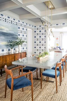 The velvet upholstered midcentury dining chairs pair perfectly with the bold blue and white wallpaper in this bright and modern dining room. See the rest of this modern and feminine redesign and total gut renovation of a historic San Francisco home on Architectural Digest.