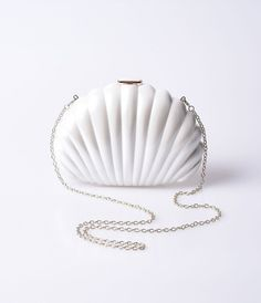 You'll be the cutest Pin-up at the shore, dear! An adorably vibrant ivory seashell wedge shaped hard clutch boasting a push lock closure with gleaming golden hardware. A detachable gold chain shoulder strap, black inner lining, and small coin pocket help