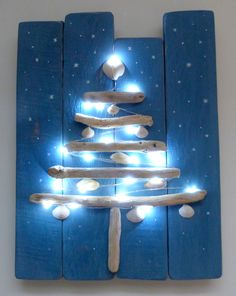 Beachcomber driftwood Christmas tree decorated with shells, sparkling lights and hand painted stars on chalk painted pallet wood.