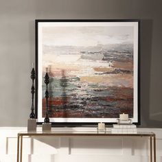 The Tides is a hand painted artwork on canvas that features a deeply textured finish using the colors of gray, tan, green, blues, soft yellow and reddish brown with an unpainted white canvas border. A wooden, black satin frame surrounds the artwork. Designed by Carolyn Kinder International.