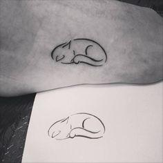 Tatuaje de un gato acurrucado situado en el exterior del pie...