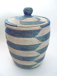 """Senegal Woven Basket - Medium Blue  $90.00. This versatile African basket adds a colorful splash of African decor to any room. A perfect storage container, it has both practical functionality and contemporary style.    The baskets are hand woven in Senegal from cattail, a grass-like plant, and colorful plastic threads which add strength and durability. Bring one home today!     Height: 22""""  Width: 14""""  Made in: Senegal"""