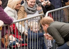 Making friends: Huge crowds gathered outside to catch a glimpse of the royal, with one little boy shaking hands with the prince
