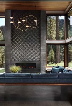 Fabulous prefabricated mountain modern home on Lake Tahoe A floor-to-ceiling fireplace, which doubles as an art piece, features dimensional tile by Daniel Ogassian. The tile is banded on either side by board-formed concrete. Home Fireplace, Living Room With Fireplace, Fireplace Surrounds, Tiled Fireplace, Grey Fireplace, Fireplace Ideas, Fireplace Feature Wall, Sunken Living Room, Fireplace Outdoor