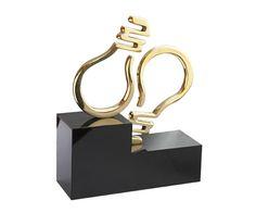 Peça: bidimensional, 10cm de altura. Materiais disponíveis: alumínio (prata) ou bronze (dourado ou patinado). Base: madeira natural ipê ou madeira revestida de fórmica preta, 14x7x5cm. Placa cortesia: aço inox (prata) ou latão (dourada), 7x2cm. Id Design, Graphic Design, Plaque Design, Trophy Design, Luminaire Design, Bronze, Sculpture Art, Signage, Sculpting