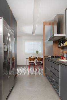 Decoração de casa. Mesa de jantar com tampo de vidro, cadeira vermelha, cadeira com encosto de madeira. Na cozinha, móvel preto com gavetas, prateleira de madeira, cooktop. #decoracao #decor #details #casadevalentina