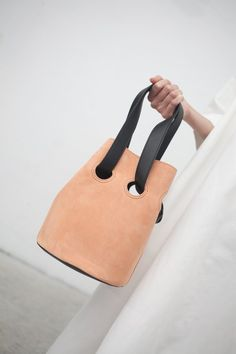 Peach suede bucket bag with leather top handles. Lined. Made in Italy. 100% leather. Structured around the idea of a uniform, Trademark's designs are made for everyday wear; smart, unfussy, yet elevated.
