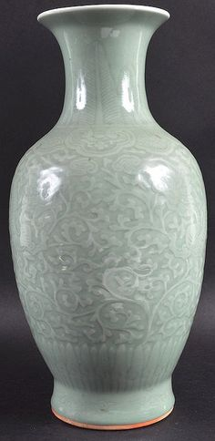 A 19TH CENTURY CHINESE GREEN CELADON PORCELAIN VASE bearing Qianlong marks to base, decorated with dragons amongst foliage. 15.5ins high.