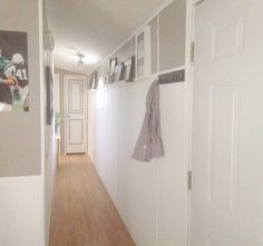 """Hallway makeover remodel manufactured mobile home single wide.  Stripes on door add dimension and create focal point. Asymmetrical walls widen the hall. White keeps the small, narrow space bright and inviting and less """"tunnel"""" like."""