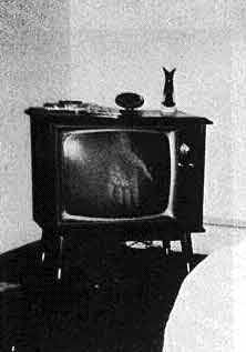 On Christmas Eve, 1968, a woman in Southern Minnesota snapped a picture of her husband assembling toys - and inadvertently preserved an unscheduled broadcast on her unplugged television set. The hand had appeared the year before, again at Christmas.