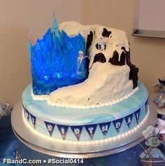 Social 0414 | Marble fondant covered base cake with ganache covered mountain and custom fondant flags come together to create an amazing Disney Frozen themed cake.  Lights were added to the castle toy set. Frozen Theme Cake, Frozen Birthday Party, Specialty Cakes, Themed Cakes, Disney Frozen, Flags, Fondant, Bakery, Marble