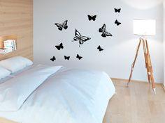Schwarze Schmetterlinge | Ein kontrastreicher Blickfang an der Schlafzimmerwand sind die schwarzen Wandtattoo-Schmetterlinge im ansonsten weißen Zimmer. TIPP: Holz kann als neutrales Gestaltungselement das Design prägen. Gute Idee? Dann schnell merken.