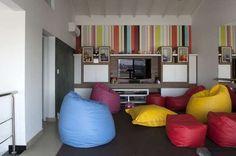 A sala de TV conta com pufes coloridos de diferentes formatos. O projeto é da arquiteta Teresa Simões. Informações: (11) 4125-0929