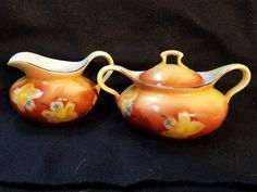 This is a Creamer and Lidded Sugar bowl. Lovely hand painted  floral design. Basically orange with yellow flowers, and gold trim. The creamer is 5 inches long, 4 inches wide and 3 inches tall. The lidded sugar bowl is 7 inches long, 4 1/2 inches wide and 4 inches tall. Marked Prov Saxe ES Germany made in the 1900,s. Perfect addition to your china collection, tea cup collection, or creamer and sugar bowl collection. No chips or cracks, some of the gold trim has some wear.         To view…