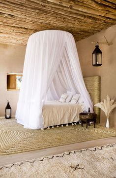 White mosquito netting, rustic wood beam ceiling, all natural colors bedroom