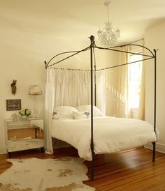 Suzie: The Iron Gate - Glam bedroom with cowhide rug, iron canopy bed, mirrored nightstand and ...